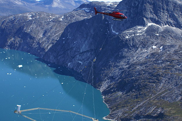 A helicopter carries SkyTEM airborne geophysical equipment over a mountain range in Greenland. SkyTEM equipment, provided by Aarhus University in Denmark, will help UW researchers locate watersheds in the Laramie and Snowy ranges during research that will begin either Sept. 10 or 11.